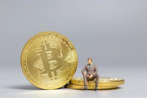 empresário em miniatura sentado sobre moedas bitcoin, conceito de investimento futuro