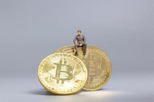empresário em miniatura sentado sobre moedas bitcoin, conceito de investimento futuro foto