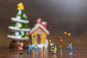 Papai Noel em miniatura e crianças segurando balões, conceito de feliz natal e feliz ano novo foto