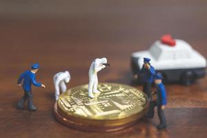 polícia em miniatura e detetives em frente à criptomoeda bitcoin, conceito de crime cibernético