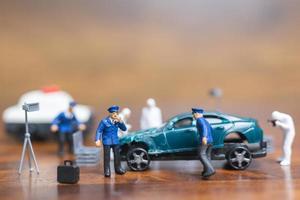 polícia em miniatura e detetive em pé ao redor de um carro, conceito de investigação da cena do crime foto