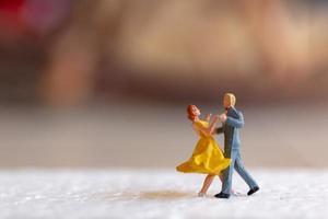 casal em miniatura dançando no chão, conceito de dia dos namorados foto