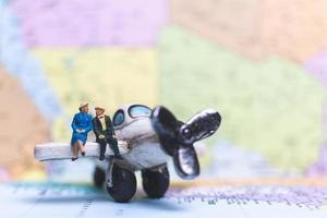 pessoas em miniatura sentadas em um avião com um fundo de mapa mundial, conceito de viagens foto
