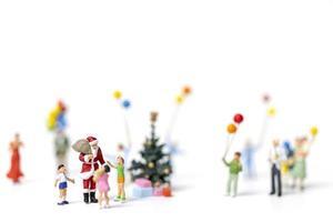 miniatura do papai noel segurando presentes para uma família feliz, conceito de natal e feliz ano novo foto