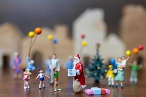Papai Noel em miniatura e uma família feliz, conceito de feliz natal e feliz ano novo foto
