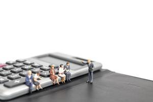 empresários em miniatura reunidos em uma calculadora isolada em um fundo branco, conceito de negócios e finanças