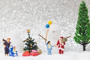 miniatura do papai noel e crianças com um fundo de neve, conceito de natal e feliz ano novo foto
