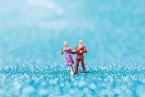 casal em miniatura dançando sobre fundo azul brilhante, conceito do dia dos namorados foto