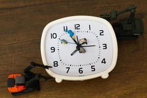 equipe em miniatura trabalhando em um despertador, conceito de tempo de trabalho foto