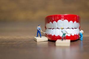 trabalhadores em miniatura consertando um dente, saúde e conceito médico