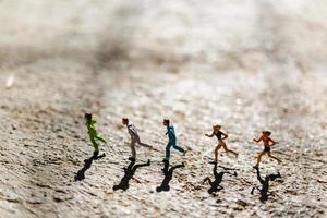 grupo em miniatura de pessoas correndo em um piso de concreto, conceito de estilo de vida saudável foto