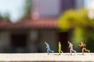 grupo em miniatura de pessoas correndo em uma estrada de concreto, conceito de estilo de vida saudável foto