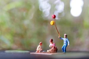 família em miniatura sentada em uma esteira durante um piquenique em um parque