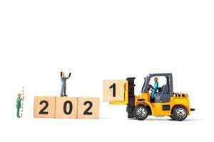 trabalhadores em miniatura se unindo para criar blocos de madeira com o número 2021, conceito de feliz ano novo foto