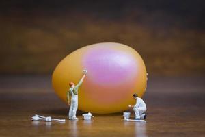 pintores em miniatura pintando ovos de páscoa em um fundo de madeira