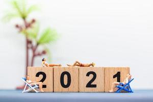 pessoas em miniatura usando maiôs sentadas em espreguiçadeiras com blocos de madeira do número 2021 foto