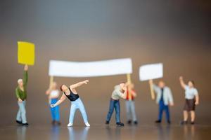 multidão em miniatura de manifestantes levantando as mãos e gritando em um fundo de madeira