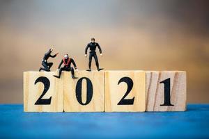 mergulhadores em miniatura mergulhando em torno de blocos de madeira com o número 2021, conceito de feliz ano novo foto
