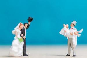 casais em miniatura em um fundo azul foto