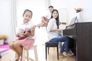 pais e filha tocando instrumentos musicais foto