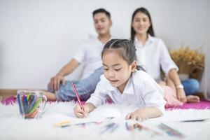 filha colorindo com os pais no fundo