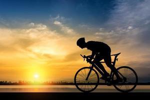 silhueta de um homem andando de bicicleta ao pôr do sol foto