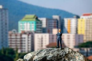 empresário em miniatura de pé em uma rocha com edifícios ao fundo
