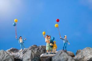 família em miniatura segurando balões em uma rocha com um fundo de céu azul