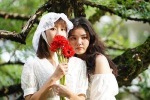 duas mulheres com gerberas vermelhas