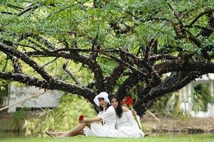 duas mulheres vestindo branco e segurando flores