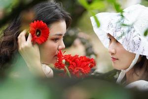 mulher colocando flores no cabelo da amiga