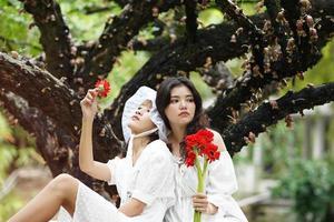 duas mulheres debaixo de uma árvore com flores