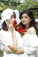 duas mulheres segurando flores de gérbera vermelha