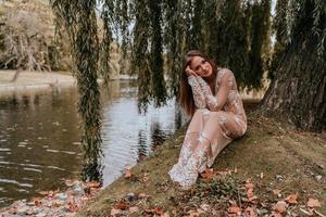 mulher posando debaixo de uma árvore perto da água