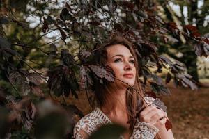 mulher posando contra uma árvore