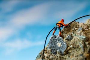 caminhantes em miniatura subindo em uma rocha, esporte e conceito de lazer