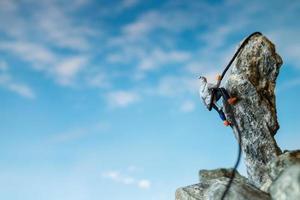 caminhantes em miniatura subindo em uma rocha, esporte e conceito de lazer foto