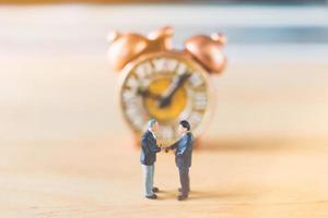 empresários em miniatura em pé com um relógio antigo em um fundo de madeira