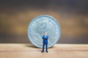 empresário em miniatura perto de uma moeda com um fundo de madeira, conceito de negócio