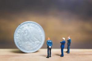 empresários em miniatura perto de uma moeda com um fundo de madeira, conceito de negócio
