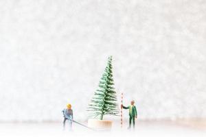 trabalhadores em miniatura preparando uma árvore de natal, conceito de decoração de natal foto