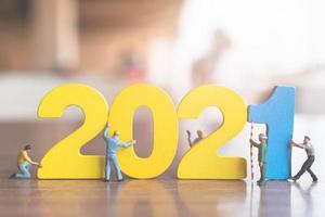 trabalhador em miniatura construindo números de madeira 2021, conceito de feliz ano novo foto