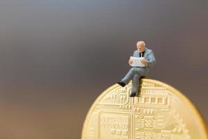 empresário em miniatura sentado em uma moeda digital, conceito de negócio