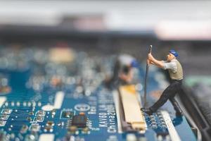 equipe em miniatura de engenheiros consertando um laptop de computador com teclado, conceito de conserto de computador