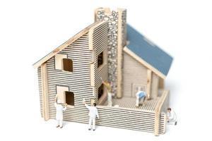 pintores em miniatura pintando uma casa de madeira em um fundo branco