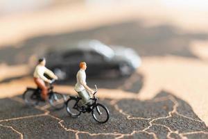 viajantes em miniatura com bicicletas no fundo de um mapa-múndi