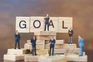 empresários em miniatura em blocos de madeira com a palavra objetivo, conceito de crescimento de carreira empresarial foto