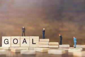 empresários em miniatura em blocos de madeira com a palavra objetivo, conceito de crescimento de carreira empresarial