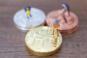 trabalhadores em miniatura fazendo criptomoeda bitcoin em um fundo de madeira