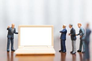 Empresários em miniatura pensando em um projeto de apresentação de investimentos em um conceito de laptop, negócio e tecnologia de computador de tela branca foto